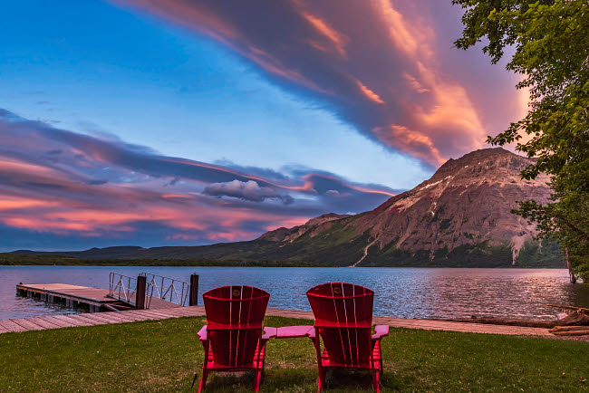 ADY200478S © Stocktrek Images, Inc. Red chairs in the sunset light at Waterton Lakes National Park, Canada.