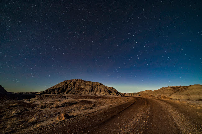 ADY200481S © Stocktrek Images, Inc. A moonlit nightscape of the badlands loop road in Dinosaur Provincial Park.