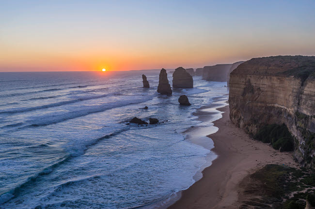 ADY200506S © Stocktrek Images, Inc. The setting Sun at the Twelve Apostles sea stacks and cliffs on the Great Ocean Road.