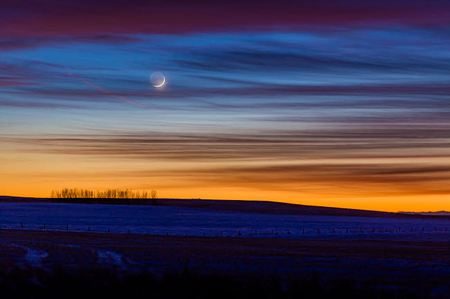 ADY200515S © Stocktrek Images, Inc. Crescent moon in colorful twilight and sunset clouds, Alberta, Canada.