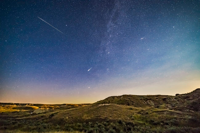 ADY200521S © Stocktrek Images, Inc. Perseid meteors over the moonlit landscape of Dinosaur Provincial Park, Alberta, Canada.