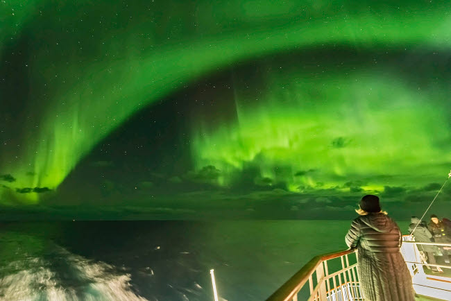 ADY200526S © Stocktrek Images, Inc. Watching the northern lights from the aft deck on a cruise ship on the coast of Norway.