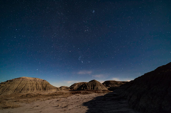 ADY200543S © Stocktrek Images, Inc. The winter stars rising over the moonlit badlands of Dinosaur Provincial Park, Alberta, Canada.