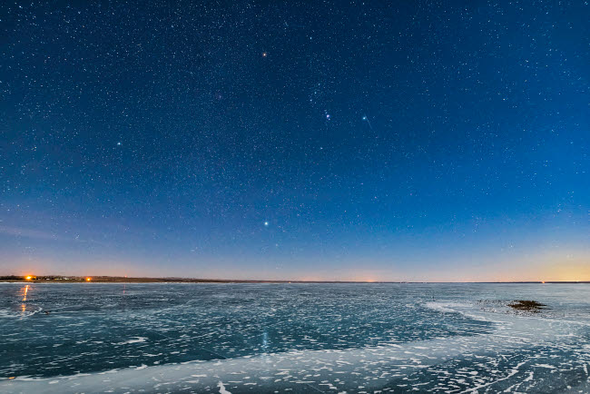 ADY200545S © Stocktrek Images, Inc. Orion and the Dog Stars rising over a frozen Lake MacGregor in southern Alberta, Canada.