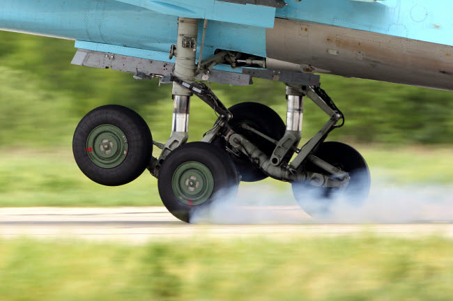 ANK100225M © Stocktrek Images, Inc. Main landing gears of Su-34 attack airplane of Russian Air Force touching runway.