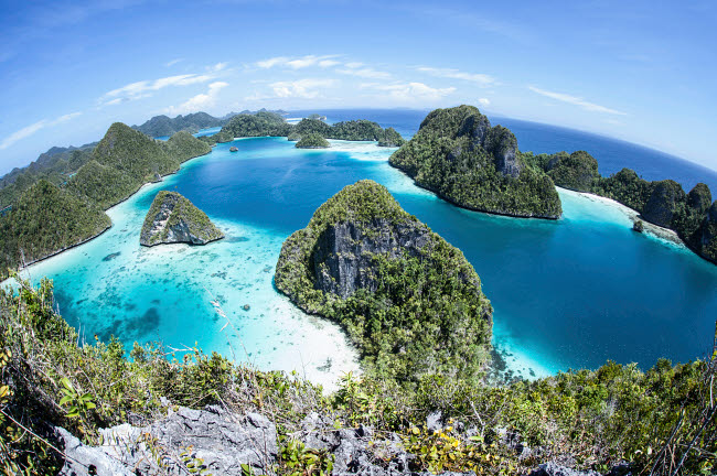 ETH400176U © Stocktrek Images, Inc. Rugged limestone islands surround a gorgeous lagoon in Raja Ampat.
