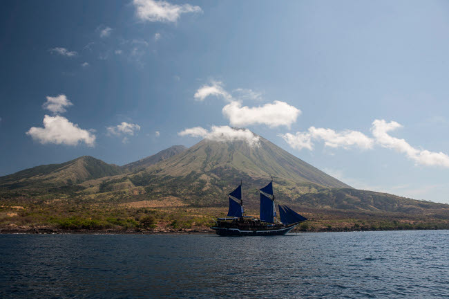ETH400587U © Stocktrek Images, Inc. An Indonesian pinisi schooner sails near a remote volcanic island.