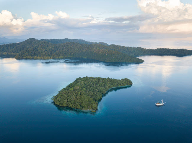 ETH401356U © Stocktrek Images, Inc. A Pinisi schooner sits at anchor in a remote area of Raja Ampat in eastern Indonesia.