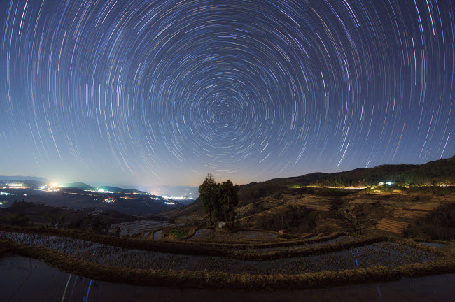 JFD200054S © Stocktrek Images, Inc. Polar star trails above Honghe Hani Rice Terraces in southwest China.