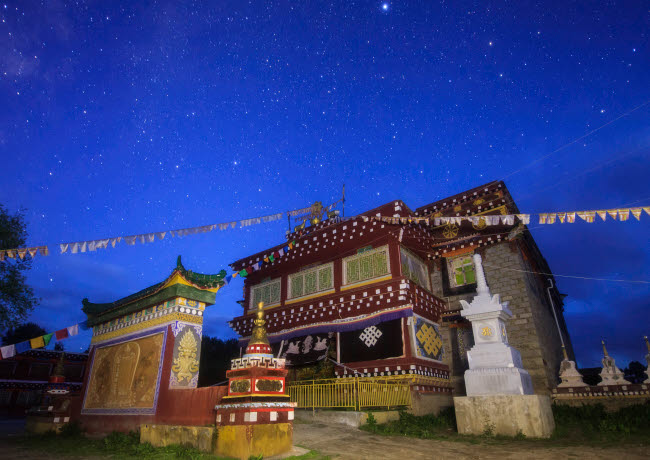 JFD200057S © Stocktrek Images, Inc. Morning twilight paints the sky in deep blue above a Tibetan temple in western China.