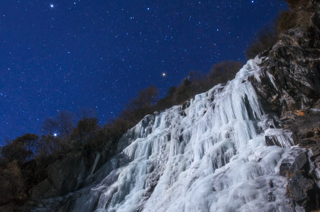 JFD200062S © Stocktrek Images, Inc. Stars shine above an icefall on a moonlit night in China.