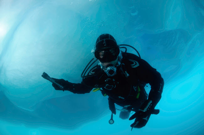 MBE400023U © Stocktrek Images, Inc. Diver by iceberg, west coast, Greenland.