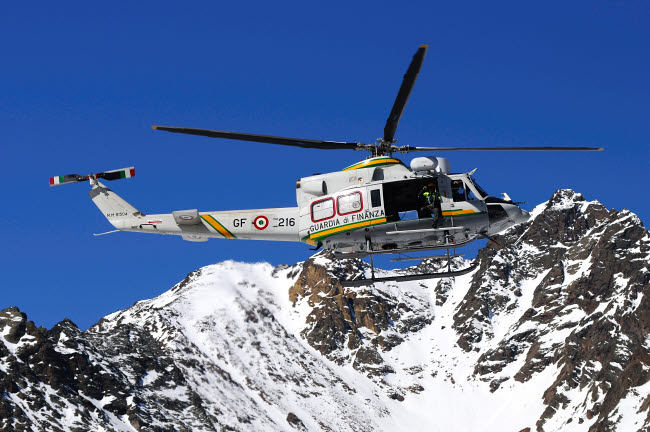 RCN100416M © Stocktrek Images, Inc. AB.412 helicopter from Guardia di Finanza flying over the Alps.