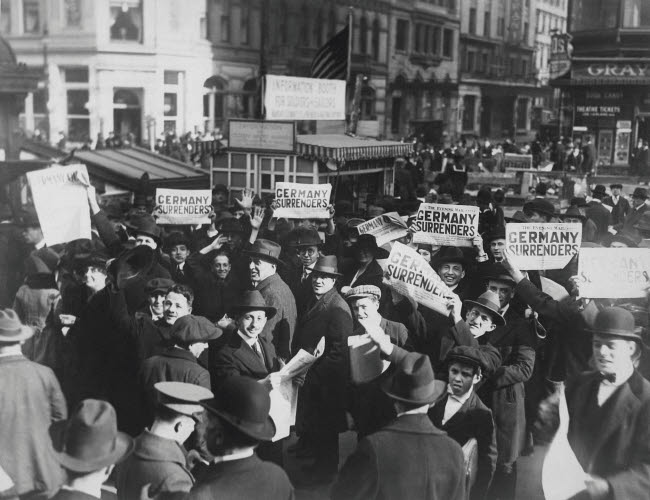 STK500275A © Stocktrek Images, Inc. Crowd at Times Square holding up Extras telling about the signing of the Armistice.