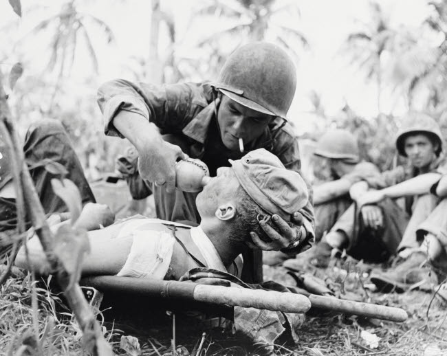 STK500706A © Stocktrek Images, Inc. Navy corpsman gives drink to a wounded Marine in Guam, 1944.