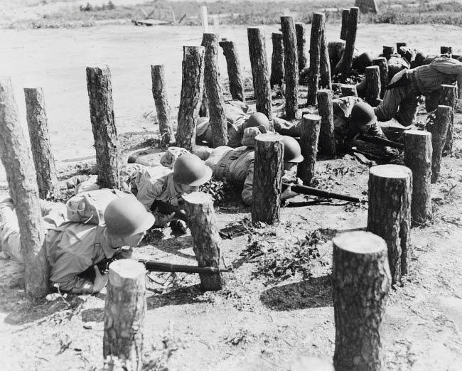 STK500749A © Stocktrek Images, Inc. Soldiers crawl through an obstacle of pine logs at Camp Edwards, Massachusetts, circa 1942.