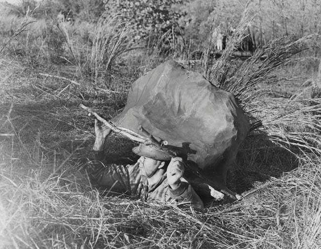 STK500778A © Stocktrek Images, Inc. American soldier emerging from a foxhole concealed by a papier mache rock, circa 1942.