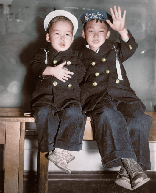 STK501386A © Stocktrek Images, Inc. Two Japanese-American boys wait for a bus to take them to an internment camp, 1942.