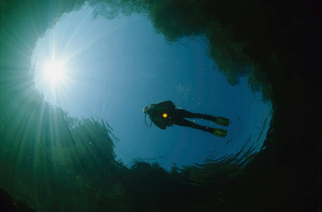 VWP401510U © Stocktrek Images, Inc. Diver floating on the river surface while sunrays shine down from above.