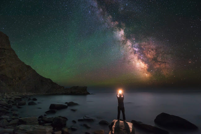 YZV200001S © Stocktrek Images, Inc. A man stands on the shore of the Black Sea at night under Milky Way.