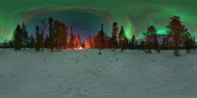 YZV200003S © Stocktrek Images, Inc. An aurora over the winter forest with glowing tent in the Kola Peninsula, Russia.