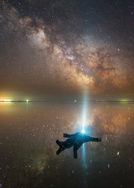 YZV200007S © Stocktrek Images, Inc. Man lying on Lake Elton  in Russia under the Milky Way while shining a flashlight up.