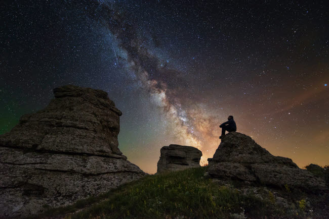 YZV200009S © Stocktrek Images, Inc. Man sits on top of Demerdzhi mountain under the Milky Way at night.