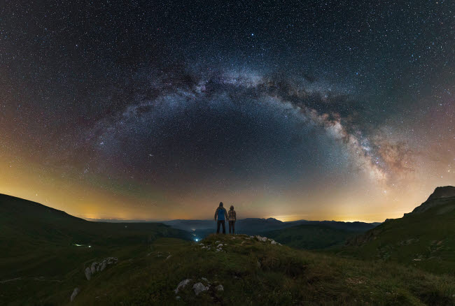 YZV200010S © Stocktrek Images, Inc. A couple gazing at the Milky Way from atop the Lago-Naki plateau overlooking Russia.