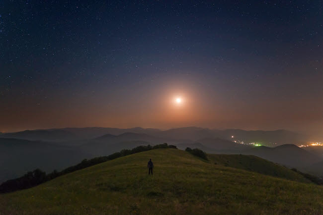 YZV200017S © Stocktrek Images, Inc. A lone man stands on the mountains at night under the moon, Sudak, Crimea.