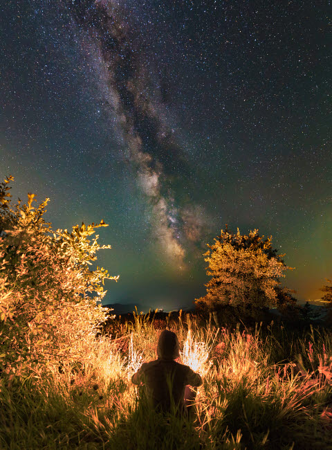 YZV200024S © Stocktrek Images, Inc. Man sitting near the campfire in the forest under the stars and Milky Way, Sudak, Crimea.