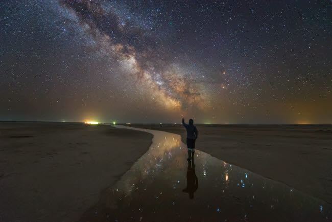 YZV200027S © Stocktrek Images, Inc. A man walking on the salt river at night under the Milky Way, Russia.