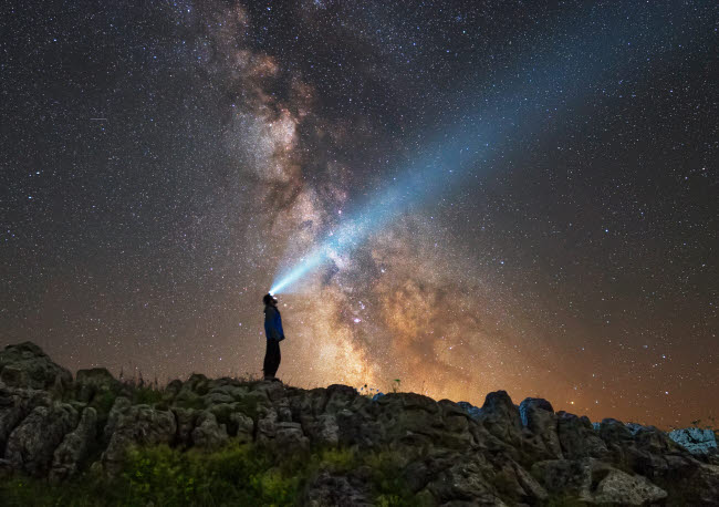 YZV200030S © Stocktrek Images, Inc. Man shining a flashlight on the Milky Way from Lago-Naki plateau in Russia.