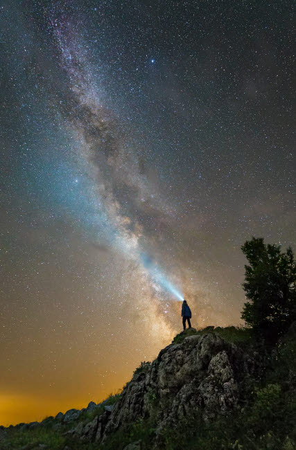 YZV200031S © Stocktrek Images, Inc. Man shining a flashlight on the Milky Way from atop a mountain in Russia.