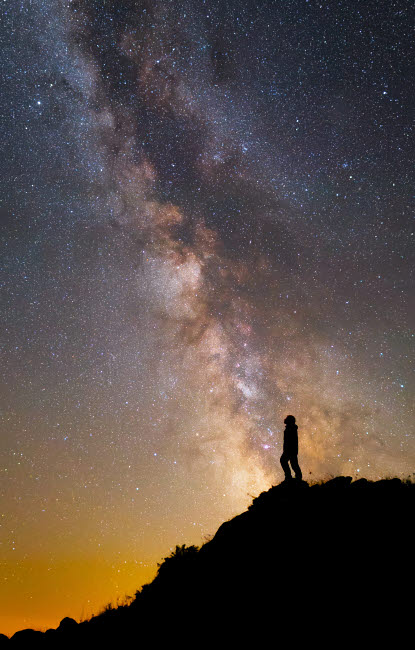 YZV200036S © Stocktrek Images, Inc. A man on a mountain under the Milky Way on the Lago-Naki plateau in Russia.